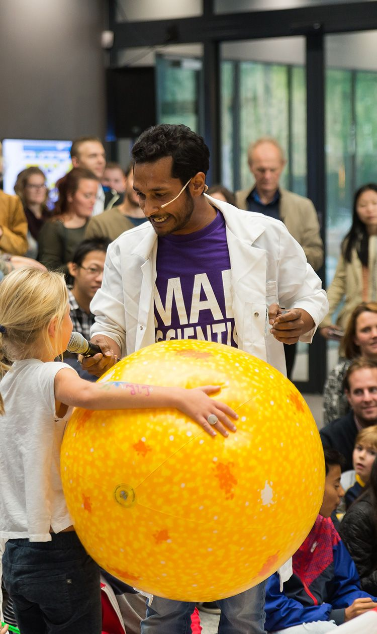 A girl in front of a large audience is holding a big yellow ball while speaking to a mad scientist holding a microphone