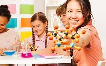 4 girls designing 3D atoms at desk with 2 beakers one blue one pink on the table